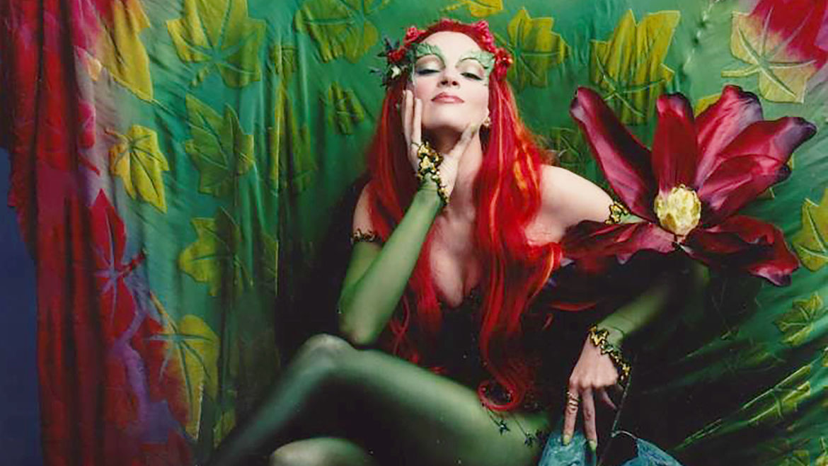 Cover Photo: A photo of Uma Thurman as Poison Ivy in the 1997 film Batman and Robin, in a leaf green body suit, sitting in a powerful but seductive pose against a nature-themed backdrop.