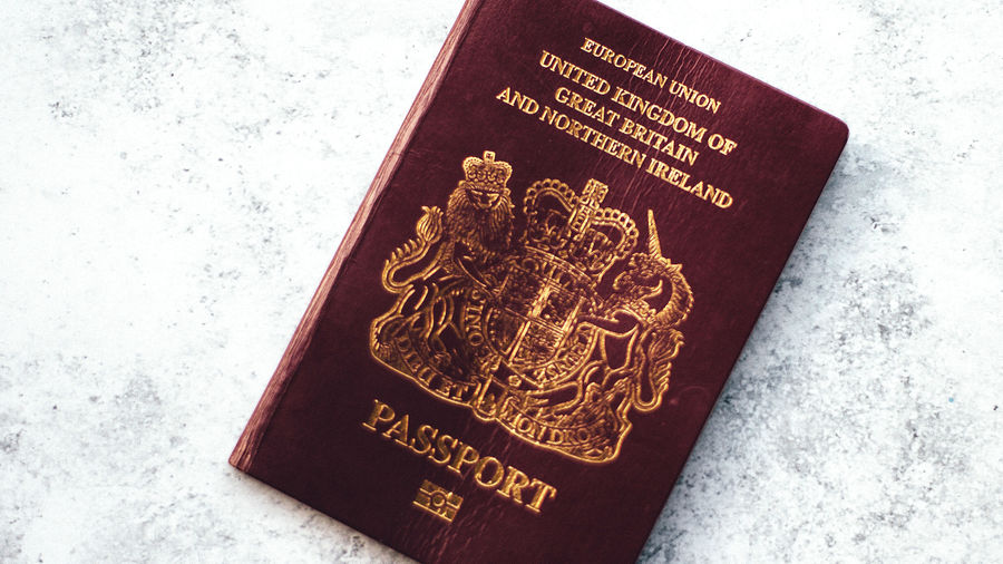 Cover Photo: A passport from the United Kingdom  on a stone surface