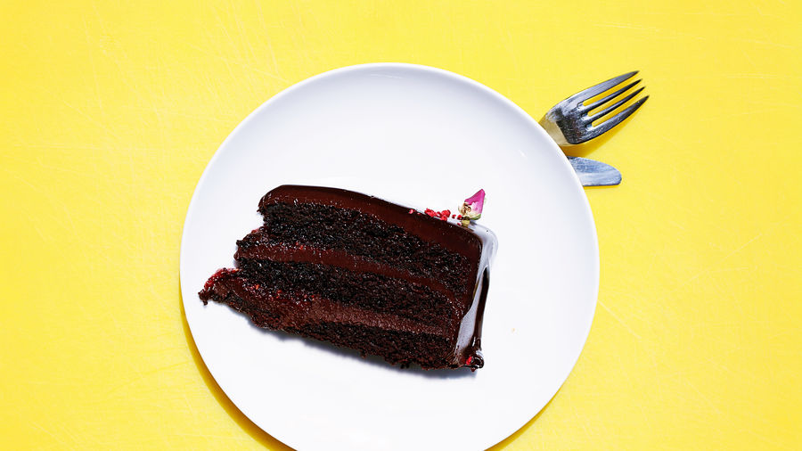 Cover Photo: A photo of a slice of chocolate cake with chocolate frosting on a white plate, concealing cutlery, on a soothing yellow background.