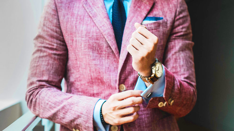 Cover Photo: A close up of a well-dressed man's suit, tie, pocket square, and watch