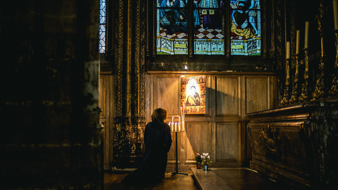 Cover Photo: A woman prays before an altar inside of a chapel.