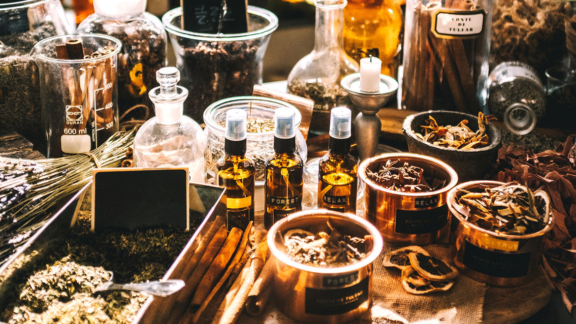 Cover Photo: An apothecary table filled with aromatic herbs, plants, and oils in different glass containers