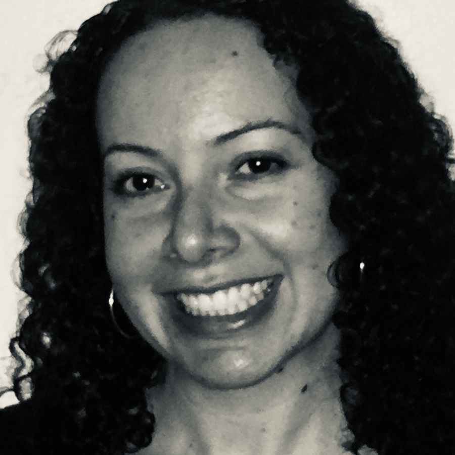 Cover Photo: Black-and-white headshot of the author. She has dark eyes and dark curly hair and she is looking into the camera and smiling