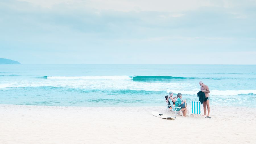 Cover Photo: This photograph shows a calm beach scene: white sand, gentle turquoise waves. On the righthand side of the picture, a group of older white folks are happily hanging out in beach chairs