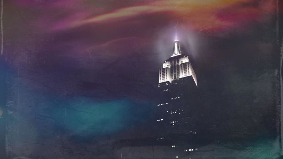 Cover Photo: This image is an edited photograph of the Empire State Building. It stands alone against a cloudy, dramatic sky painted in pinks and oranges and yellows fading into purple and turquoise