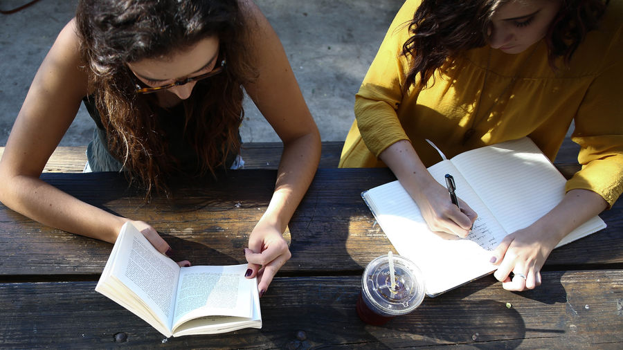 Cover Photo: Two young women sit at an outside table in the sun. One is reading a book and one is taking notes in a journal and drinking a to-go cup of coffee.