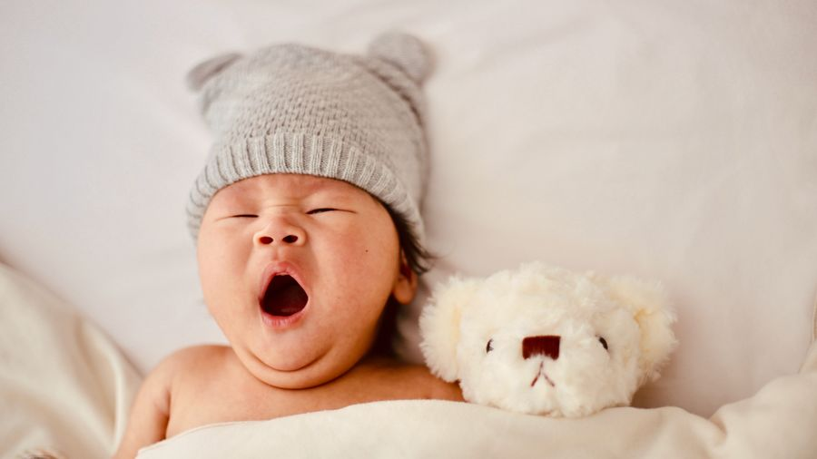 Cover Photo: photograph of a newborn baby yawning, tucked under a sheet with a  white teddy bear