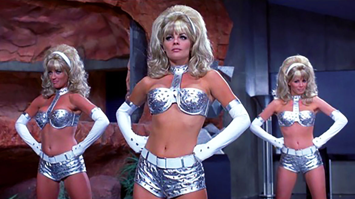 """Cover Photo: a still of three """"femmebots"""" from the movie Austin Powers: International Man of Mystery"""