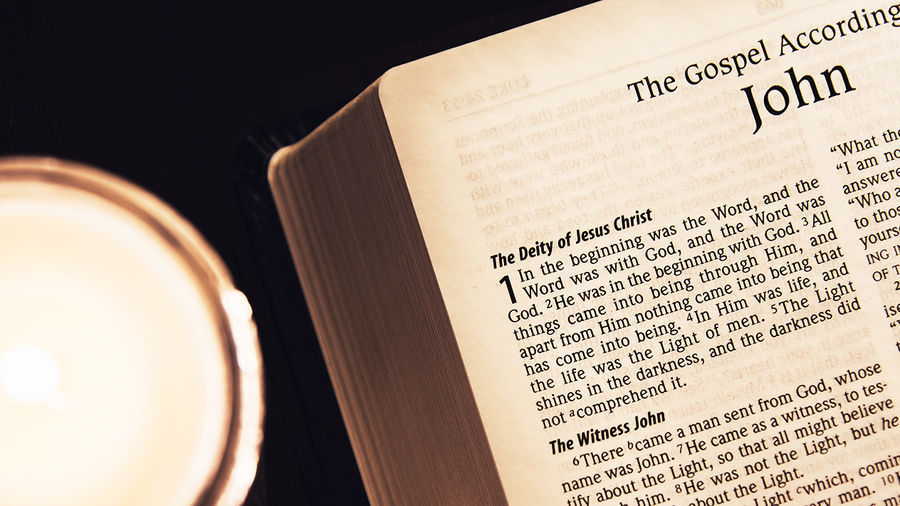 Cover Photo: photo of Bible, opened to the Gospel of John, next to a candle