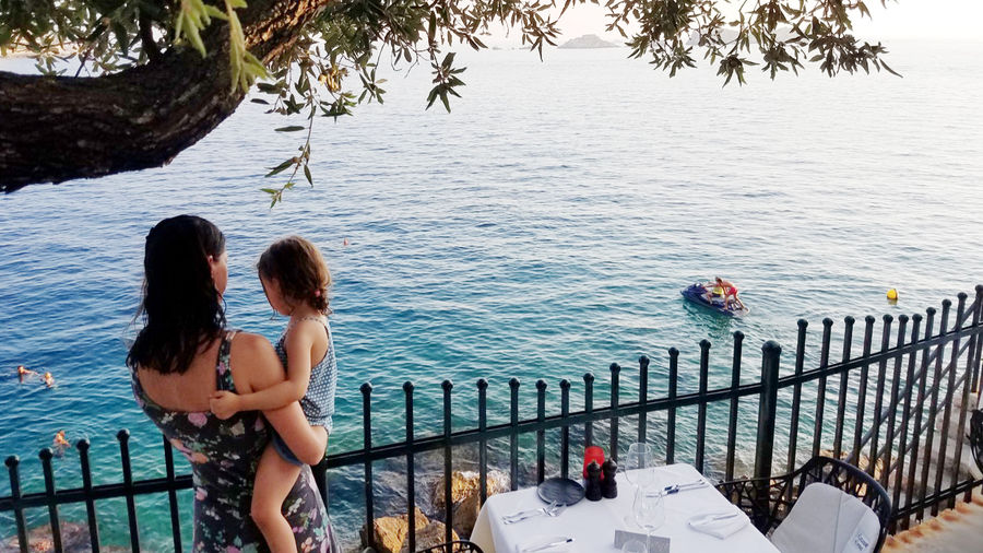Cover Photo: A mother and her daughter overlooking a coastline in Croatia, with a dinner table beside them