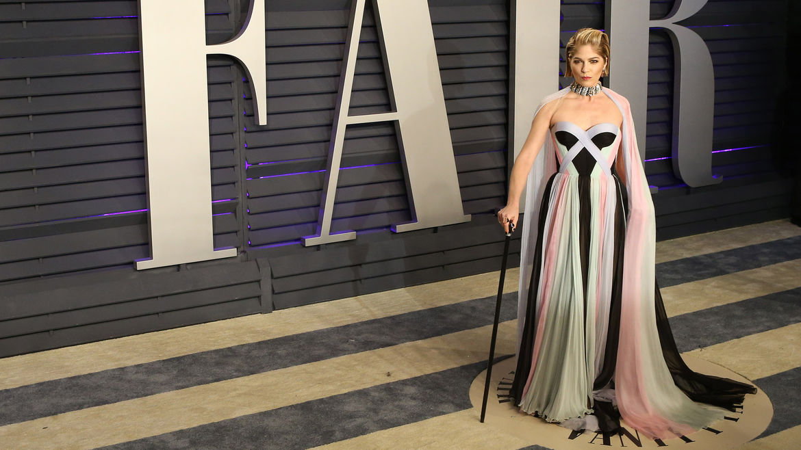 Cover Photo: A photo of Selma Blair in front of the Vanity Fair building, dressed in a flowing black, pink, blue, and mint green gown, posing with her cane.