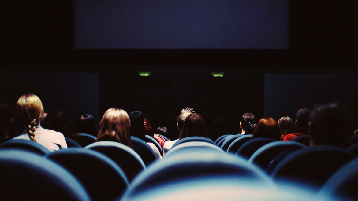 Cover Photo: People sitting in a movie theater looking at the screen.