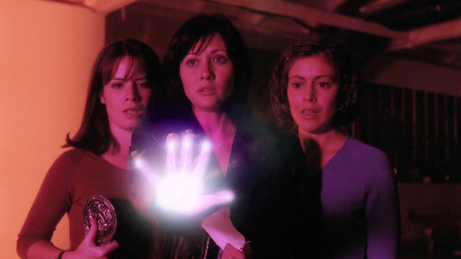 Cover Photo: A screencap of Charmed, where the three Halliwell sisters are standing together in fear, one about to use her powers, sending a surge of light toward her hand.