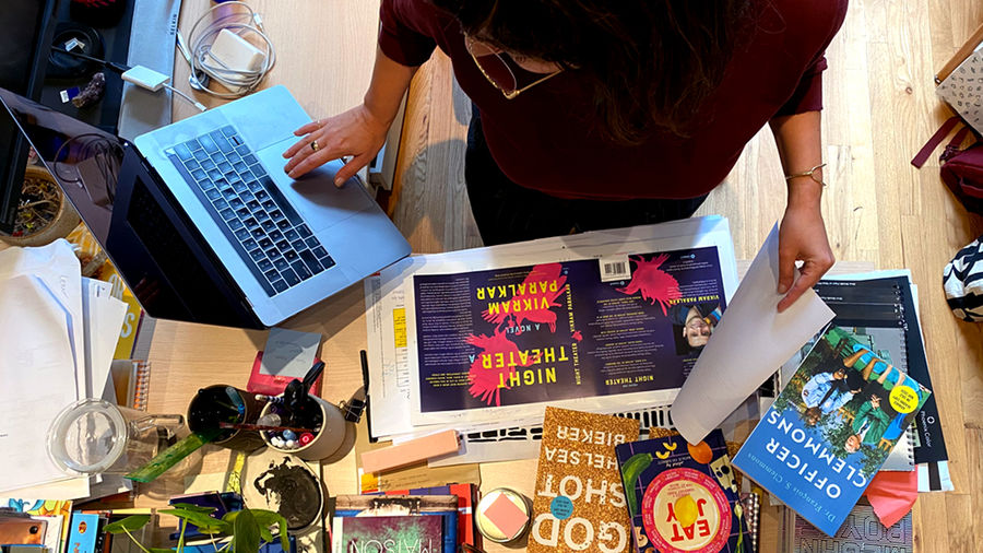 Cover Photo: photo of Catapult creative director Nicole Caputo working at her desk, with laptop, designs, and book covers