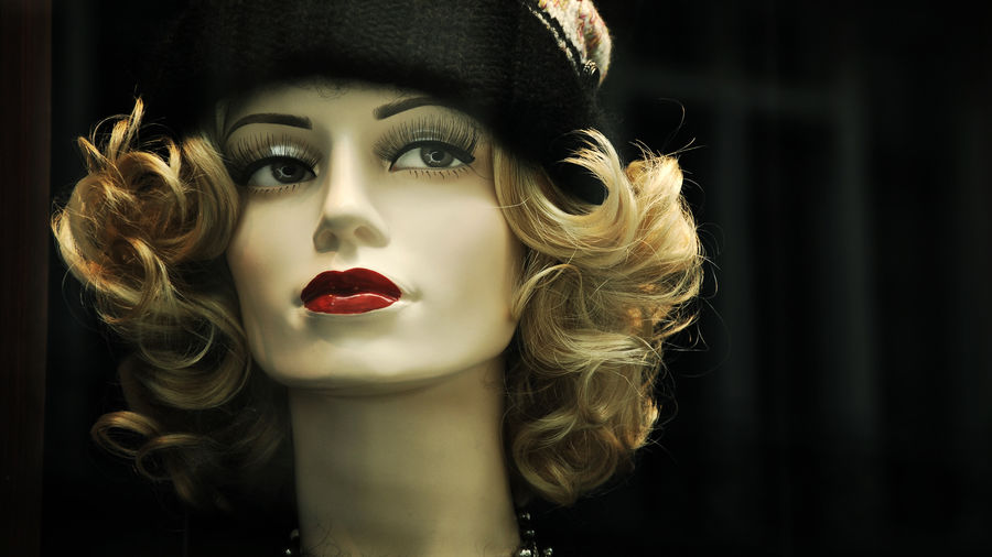 Cover Photo: A mannequin head with dark lips the color of blood and exaggerated eyelashes, wearing a wig and a knit cap