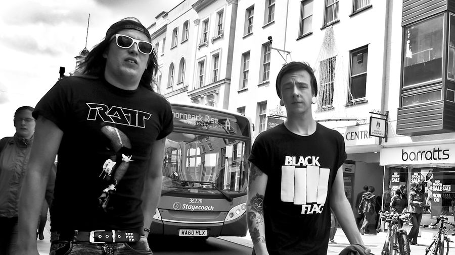Cover Photo: Two men leaving a punk show near Liverpool, one with a Black Flag t-shirt and plugs, another with a RATT t-shirt and sunglasses. The photo is in black-and-white.