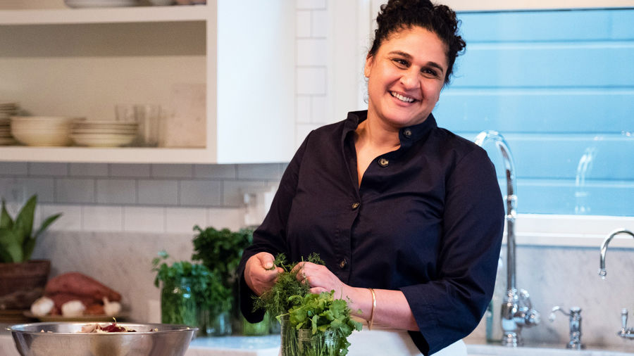Cover Photo: An image of Samin Nosrat in a white kitchen, smiling beatifically at someone just off-screen, as she adds herbs to a bowl of ingredients for a dinner on Salt Fat Acid Heat.