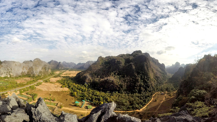 Cover Photo: A panoramic view of the mountainous countryside of Laos: rocky crags covered in lush trees, wide open fields, and a bright sky blanketed with fluffy clouds