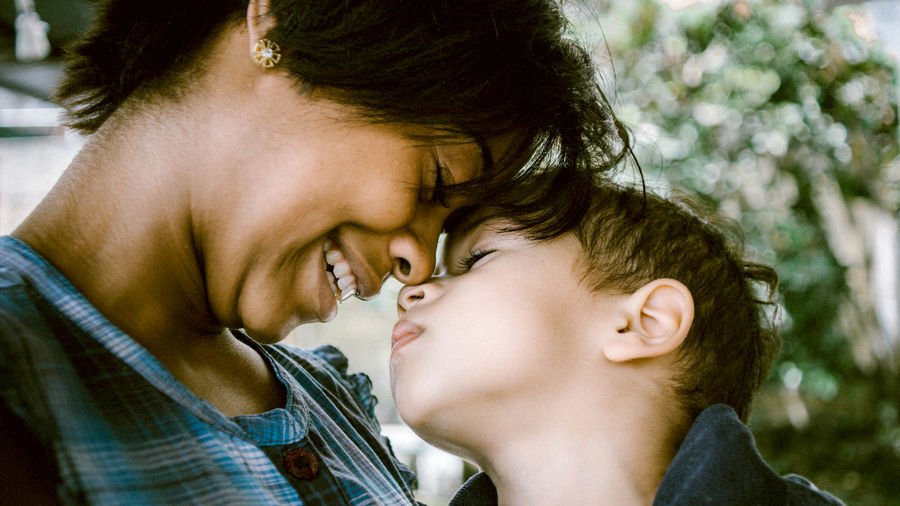Cover Photo: A smiling black mother in a casual but loving embrace with her young son, whose eyes are closed in a dreamy expression.