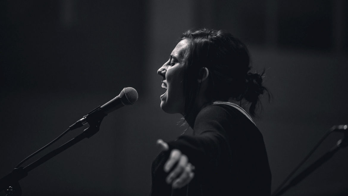 Cover Photo: A black and white photo of a woman singing passionately in front of a microphone.
