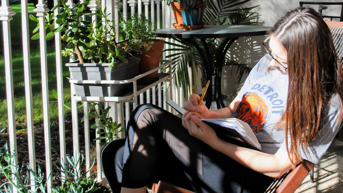 Cover Photo: Sara Wong sits on a porch, surrounded by plants. Sun and shadow fall on her as she draws her in notebook.