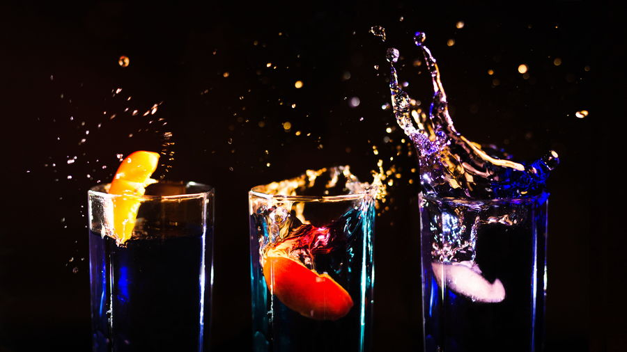 Cover Photo: Three shot glasses full of clear alcohol against a black background,  a different slice of fruit diving into each, lighting the drink up with their neon glows—orange, red, blue—splashing brightly into the darkness.
