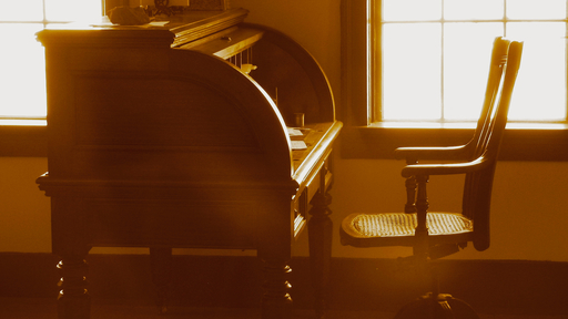 Cover Photo: A sepia photo of a wood writing desk and empty chair in an empty room, sunlight streaming through the windows.