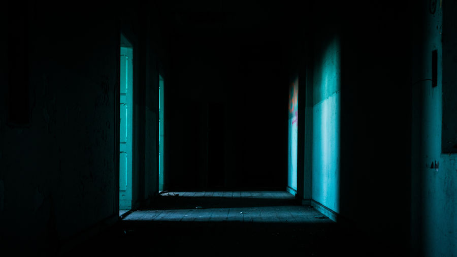 Cover Photo: Dark shadowy corridor with stripes of light entering the space from open doors