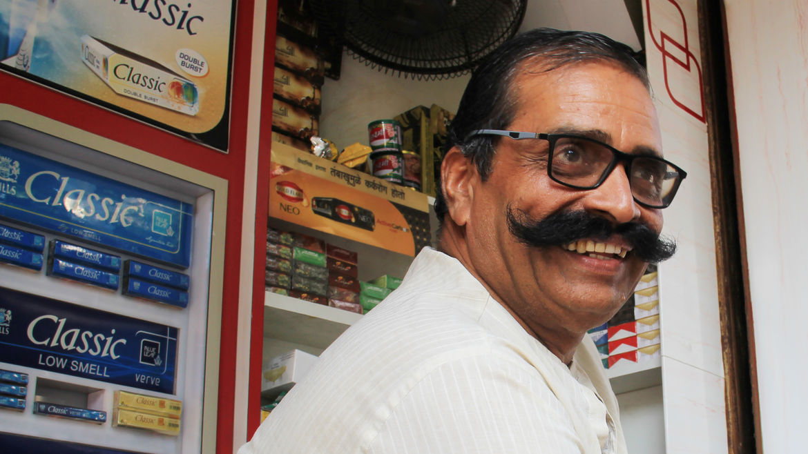 Cover Photo: An image of the interview subject, a smiling man with a distinguished mustache