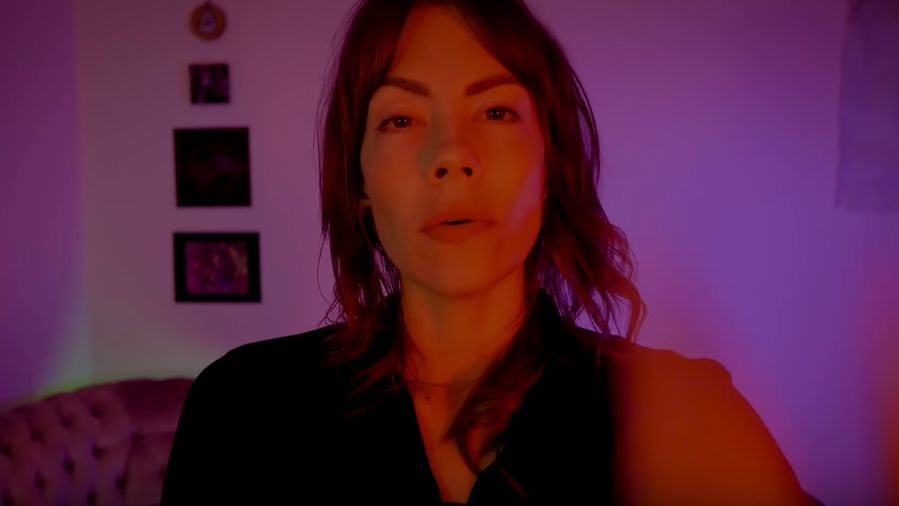Cover Photo: A screencap of ASMRtist and Youtuber, The Lune Innate, speaking to the viewer and moving her hand across the image. She is standing in front of a glowing, soothing purple background, fading into oranges and reds as though picking up on their energy, or like an overexposed photo.