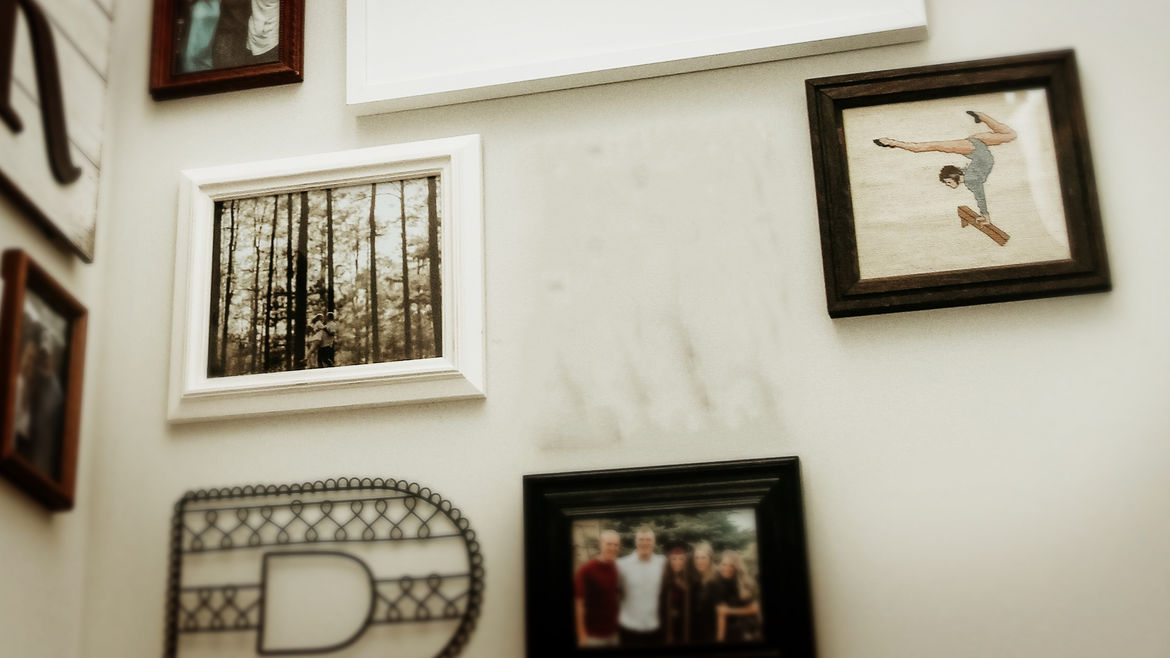 Cover Photo: A photo of a wall crowded with framed family pictures, and one blank space where it is clear another framed photo hung before.