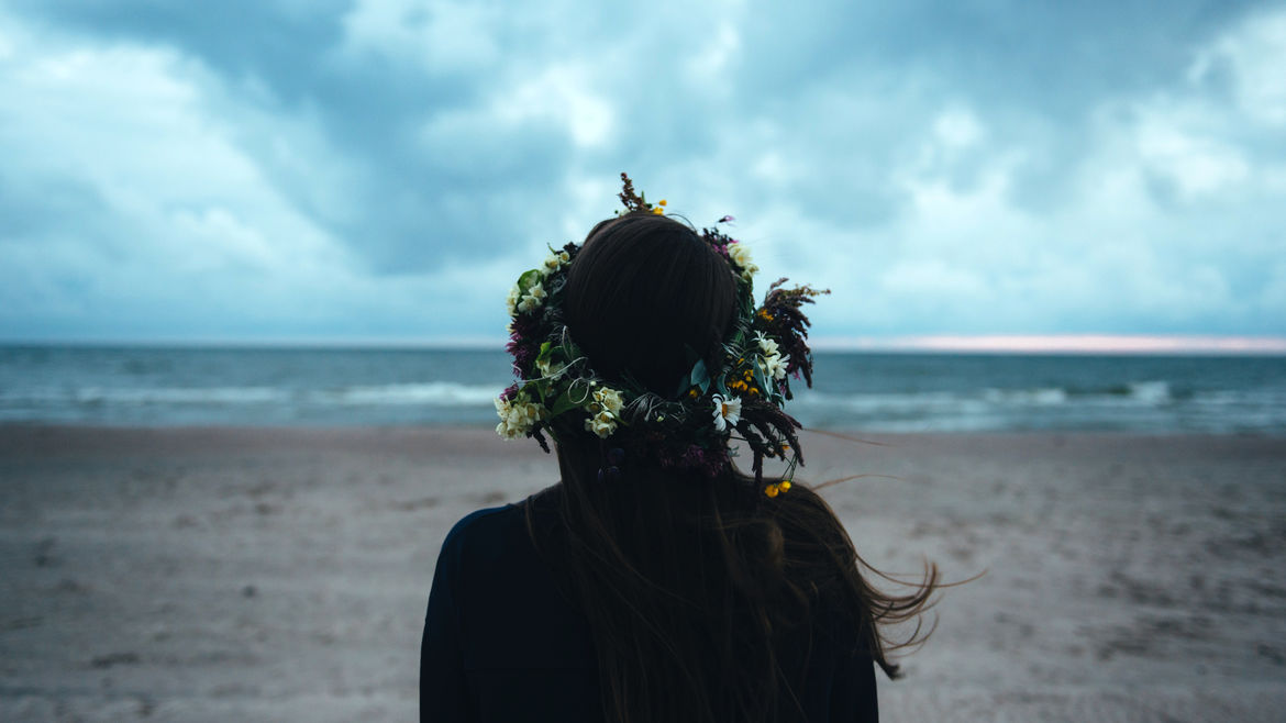 Cover Photo: A photo of a woman from behind, facing the beach, a flower crown on her head. There is the air of something just about to happen.