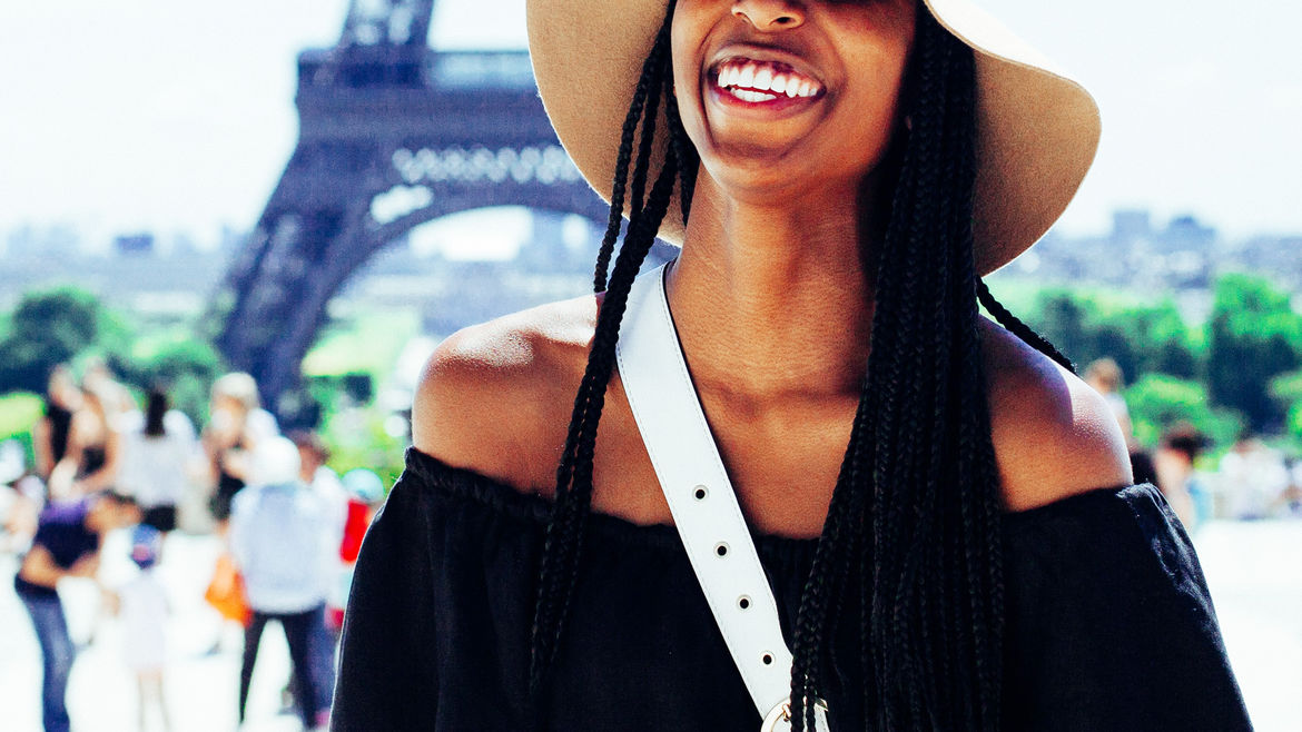 Cover Photo: An image of a black woman smiling in front of the Eiffel Tower in Paris, France