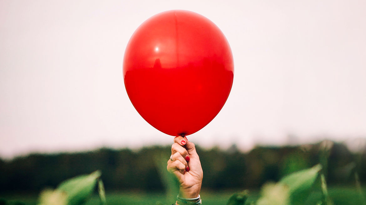 Cover Photo: A balloon being held up in the middle of a field