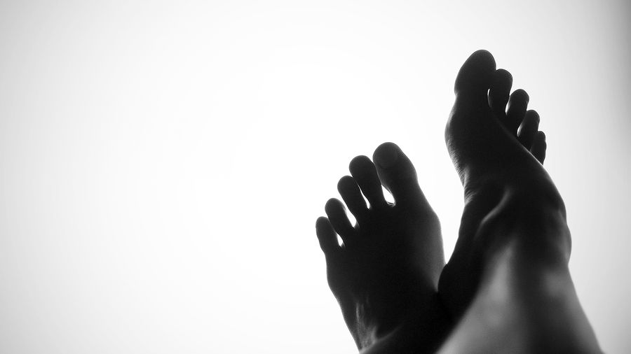 Cover Photo: photograph of a pair of feet in shadow against a white/grey background