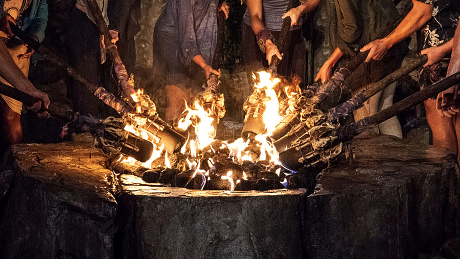 Cover Photo: An image of adults lighting torches from a communal fire pit, from the reality competition television show Survivor