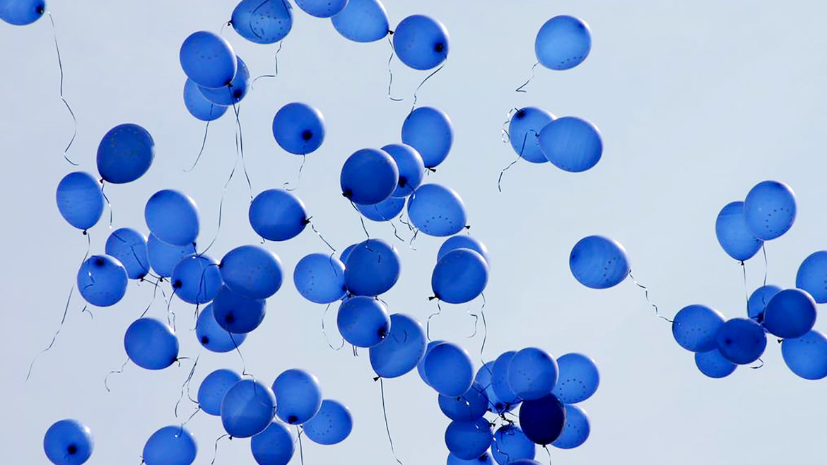 Cover Photo: Dozens of blue-for-boys balloons are released against a stormy sky