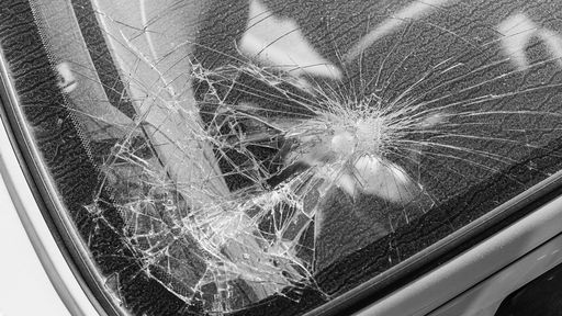 Cover Photo: A close-up black-and-white photo of the shattered window of a car.