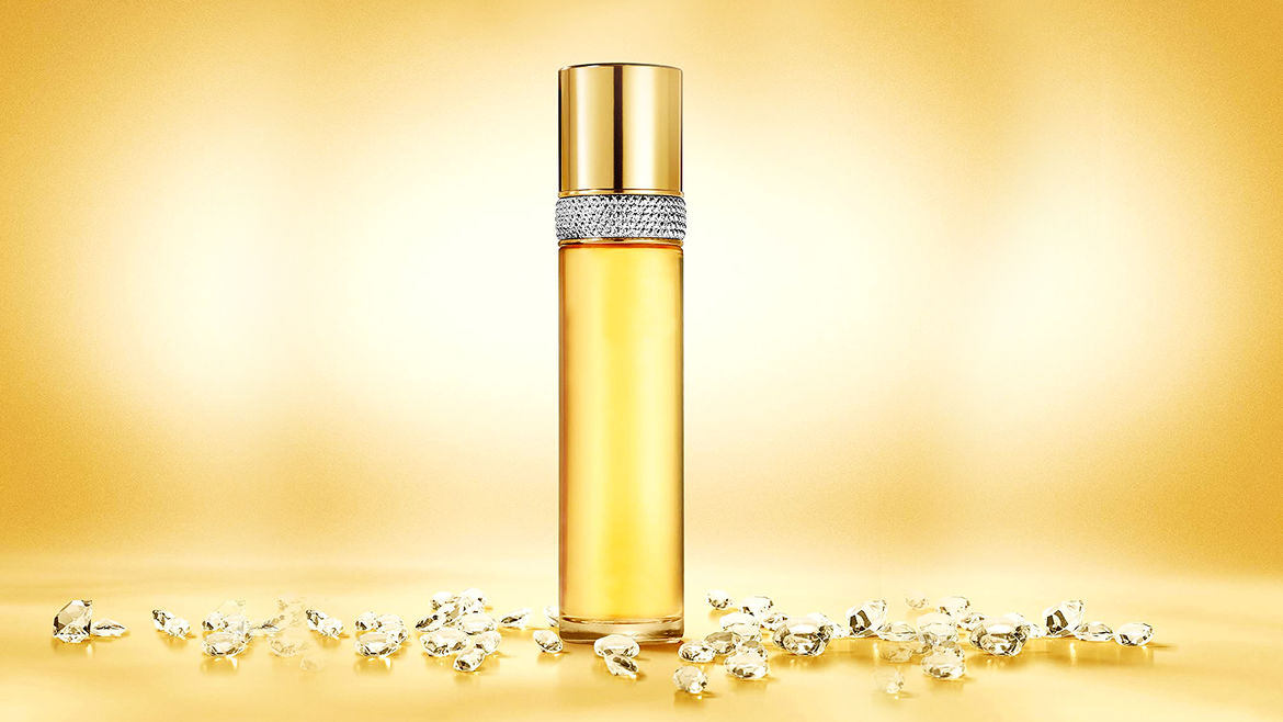 Cover Photo: A photograph of a bottle of the perfume Elizabeth Taylor White Diamonds: a sleek elegant tube of clear fluid with a band of faux diamonds at the neck