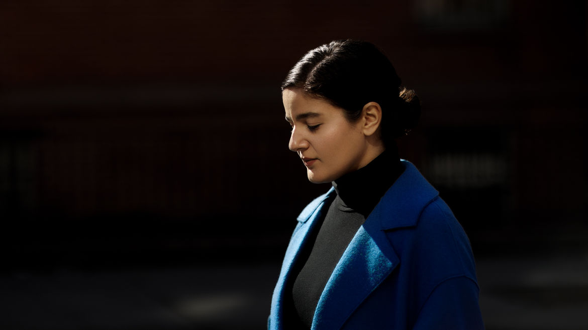 Cover Photo: This photograph of the author is striking, with a dark background. The only light in the photograph is clear and clean, and hits the author's face and blue wool jacket, as she looks down with eyes closed, as if steeling herself during a moment of strong emotion