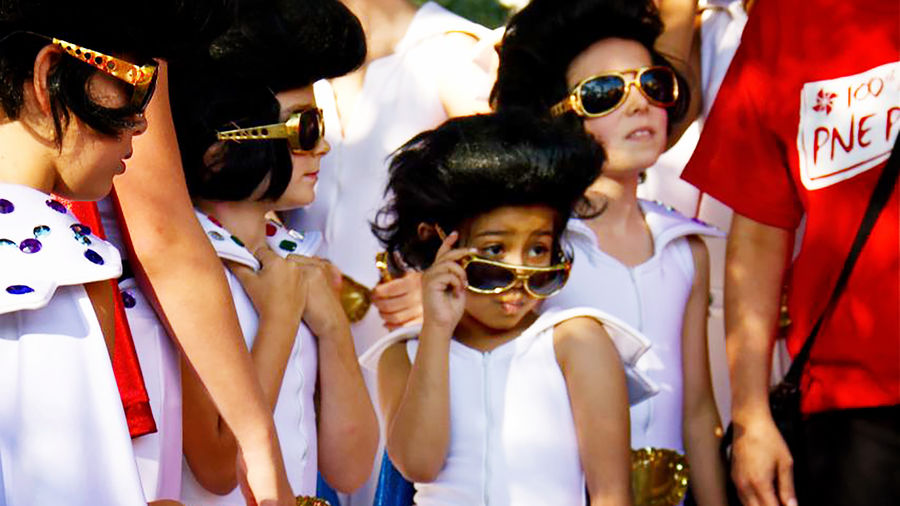 Cover Photo: A crowd of children dressed as Elvis Presley, the child in the center lowering their Elvis sunglasses to give someone just off-camera a mock-flirtatious look.