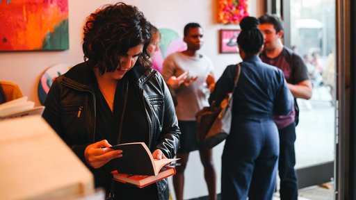 Cover Photo: photograph of a young person with dark curly hair and a leather jacket reading a book at a bookstore, with other customers in the background (photo by Sloane Dakota Tucker for Duende District)