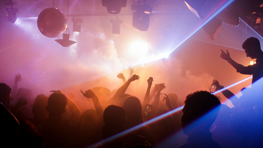 Cover Photo: Many people are on a dance floor; their faces are eclipsed in the dark, but the bright colors of purple, orange, and hues of blue fill the room along with smoke.