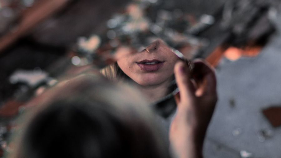 "Cover Photo: In this photograph, a young woman holds a shattered mirror up to her face. As the viewers, we ""stand"" behind her and see the lower half of her face reflected back in the biggest shard."