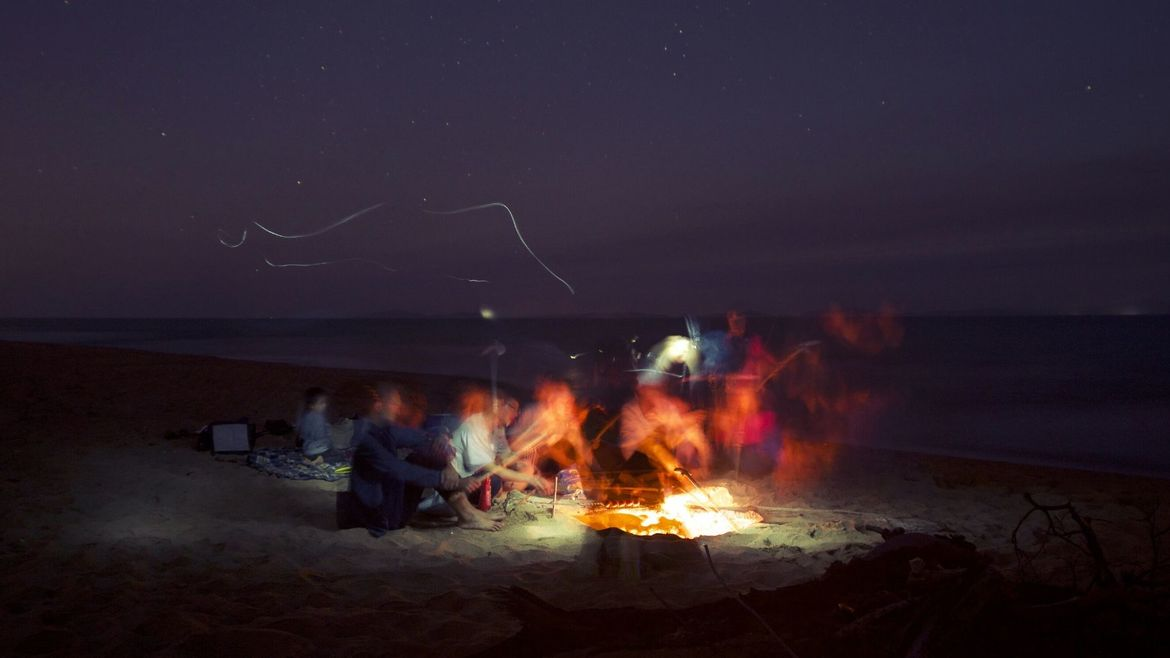 Cover Photo: An image of people gathered around a bonfire at a beach in the calm of night, blurred as the flames reach toward the sky.