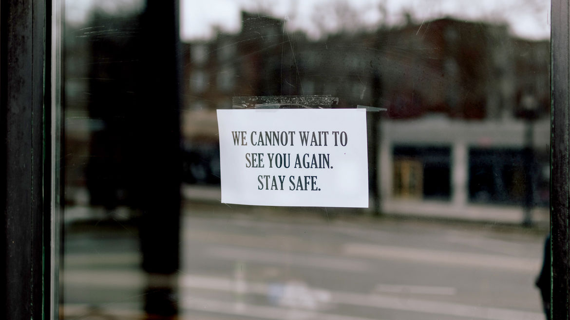 "Cover Photo: A sign taped to a door that reads ""We cannot wait to see you again. Stay safe"""