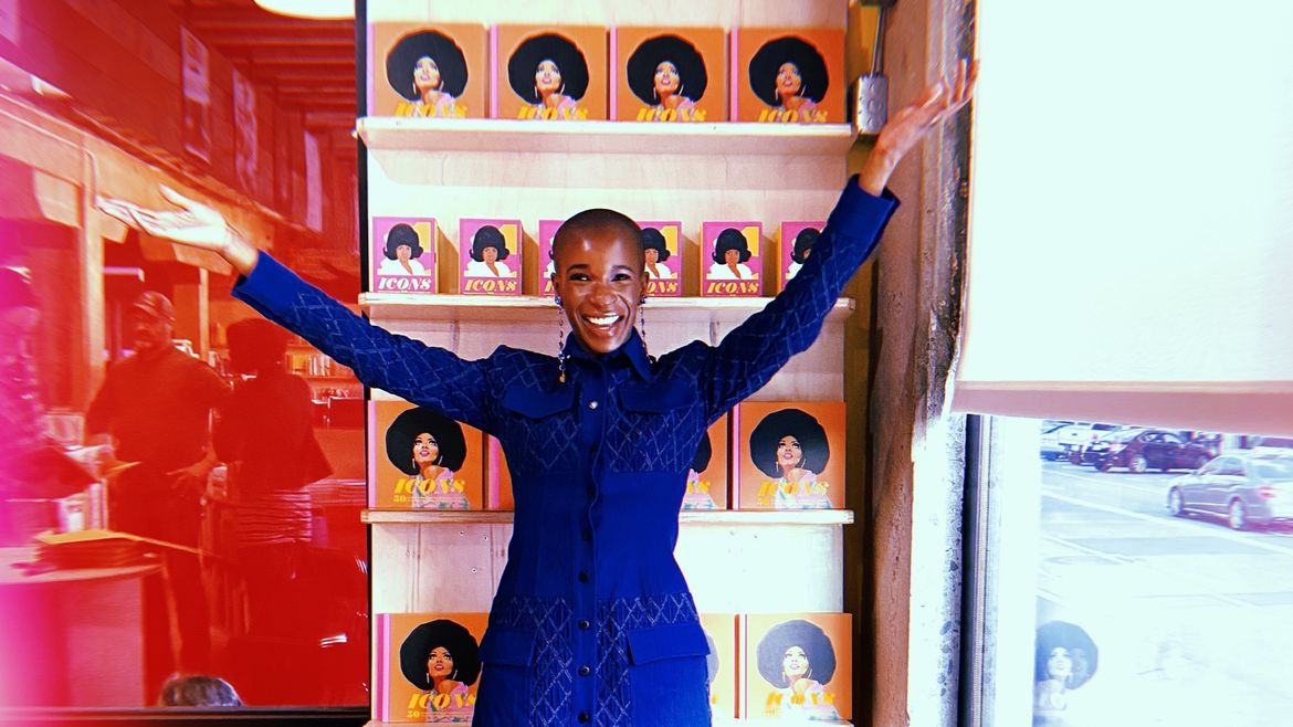 Cover Photo: A photograph of a Black American woman in front of portraits she illustrated that depict iconic Black women of American culture