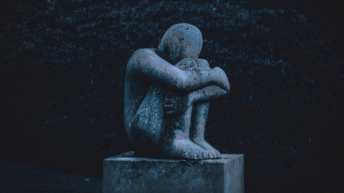 Cover Photo: Against a dark background is a stone statue of a person sitting in the fetal position, their face hidden by their knees.