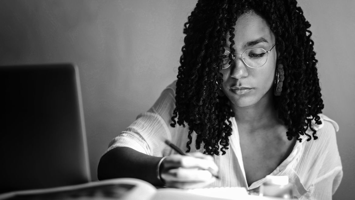 Cover Photo: A photo of a Black woman working at a desk with books, pens, and a laptop, in deep thought