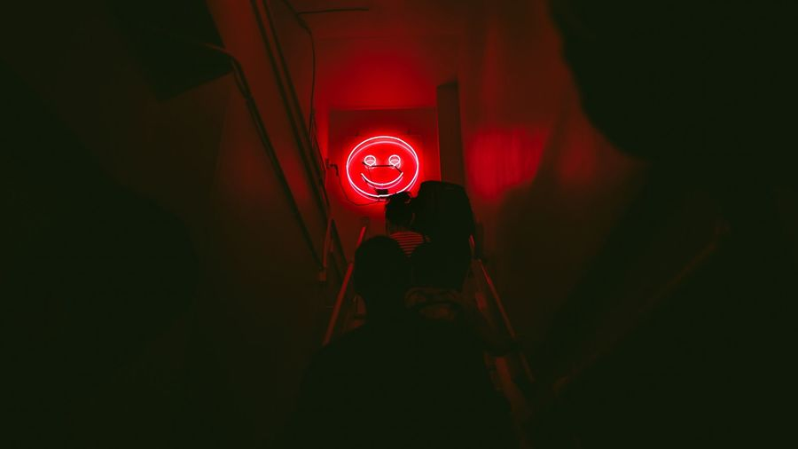 Cover Photo: A photo of a dark staircase bathed in the pink neon light of a sign shaped like an unsettling smiley face.
